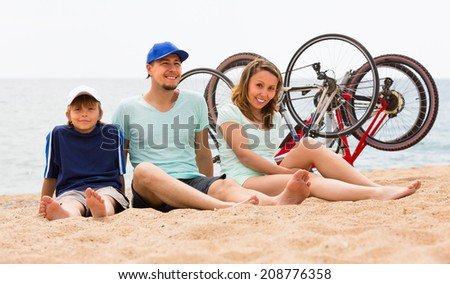 Positive parents and boy sitting on sand with bicycles  - stock photo