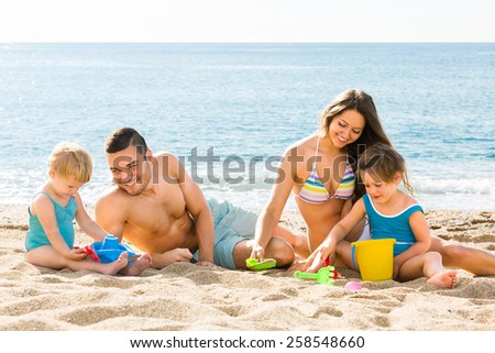 Positive parents helping toddlers to dig sand at beach - stock photo