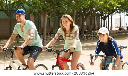 Positive parents with kid riding bicycles in park and smiling - stock photo