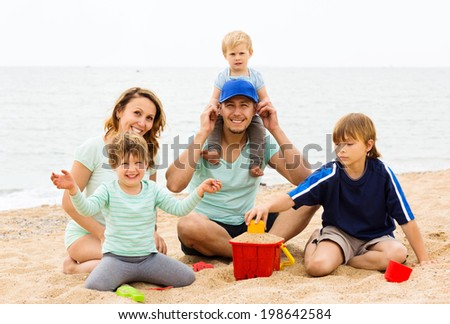 Positive parents with kids on vacation sitting at sandy beach - stock photo