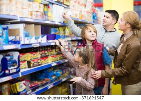 positive  parents with two kids choosing crispy flakes in shop