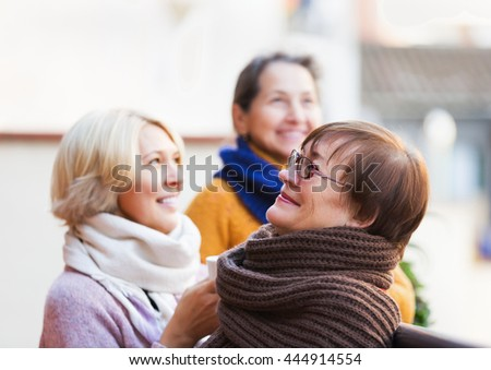 Positive pensioners in warm clothes having cup of hot tea on terrace. Focus on brunette woman