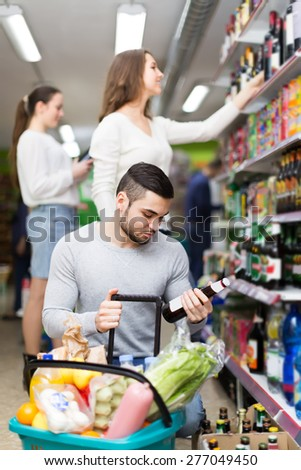 Positive people buying bottles of  beer  at food shop - stock photo