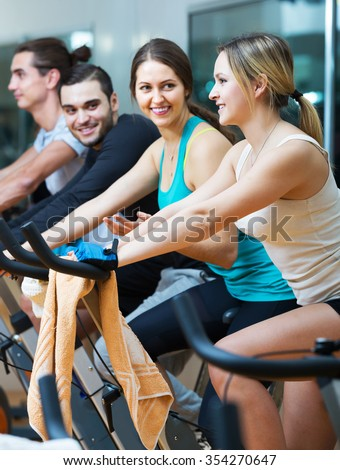 Positive people training on exercise bikes in gym