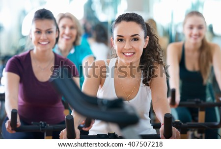 Positive pleasant  elderly and young women working out hard in sport club