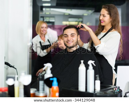 Positive professional adult woman hairdresser doing hairstyle for young men