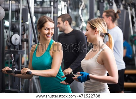 positive russian adults having strength training under coach control in gym