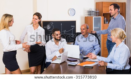 Positive russian colleagues discussing price development at office - stock photo