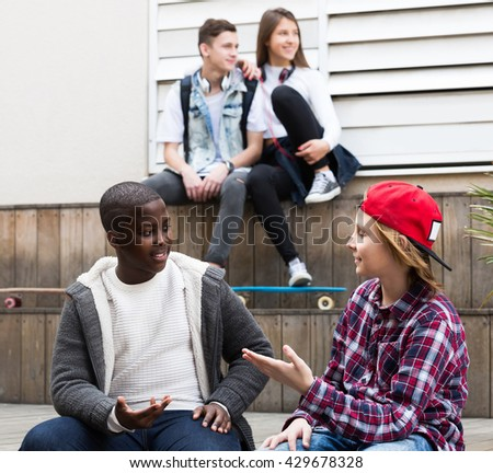positive Russian girl and three boys hanging out outdoors and discussing something