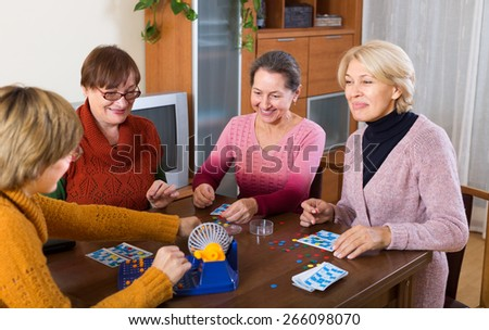 Positive 60s senior female friends   sitting at desk with lotto - stock photo