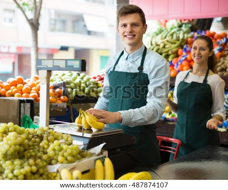 Positive sellers weighing stems of sweet bananas at fruit market and smiling