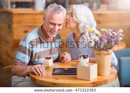 Positive senior couple resting in the cafe