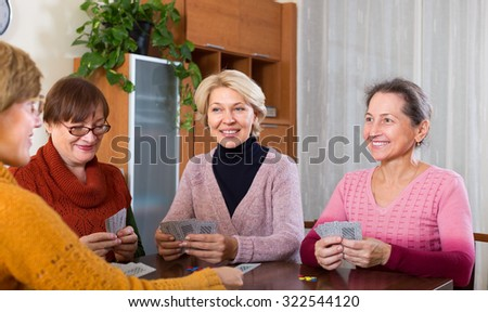 Positive 55-60 senior female friends staking money during bridge - stock photo