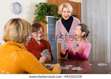 Positive senior female friends staking money during bridge in apartment