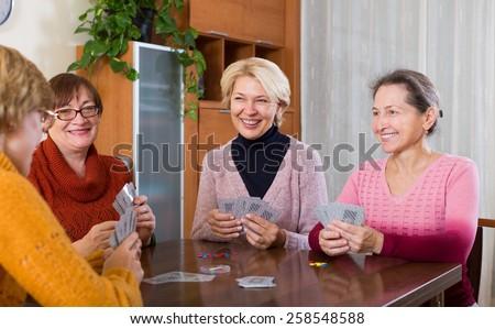 Positive senior female friends staking money during bridgein inside - stock photo
