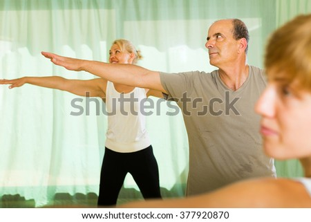 Positive senior mature couple practicing body bending at gym