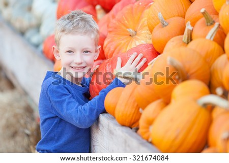 positive smiling boy choosing pumpkin at fall festival, pumpkin patch or farmers market - stock photo