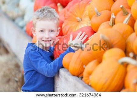 positive smiling boy choosing pumpkin at fall festival, pumpkin patch or farmers market - stock photo
