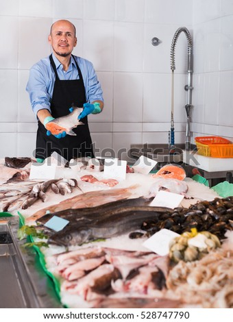Positive smiling cheerful mature salesman with apron offering fresh fish in shop