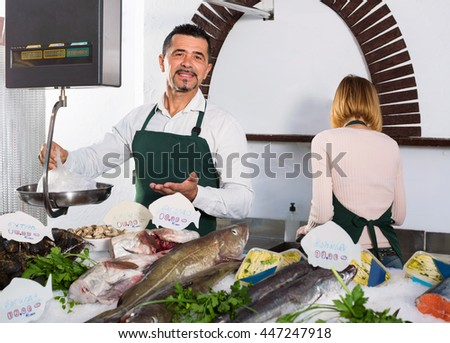 Positive smiling cheerful shop assistants selling fresh fish and chilled seafood