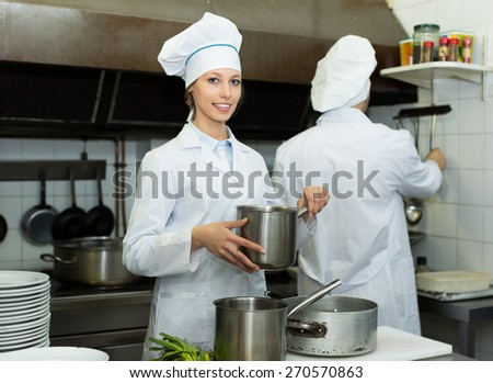 Positive smiling chef and assistant preparing meal in cafe