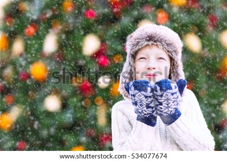 positive smiling child in trapper hat and warm winter clothes blowing snow, having fun and enjoying christmas time by the tree