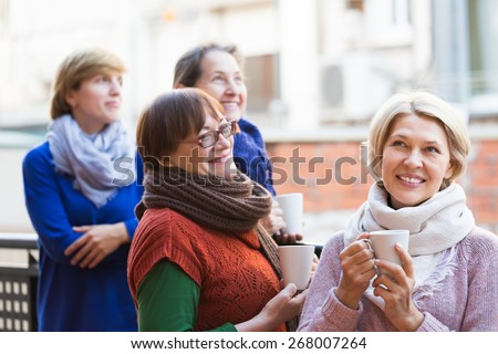 Positive smiling elderly women drinking coffee at patio. Focus on blonde  - stock photo