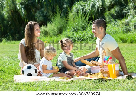 Positive smiling family of four on picnic at summer day