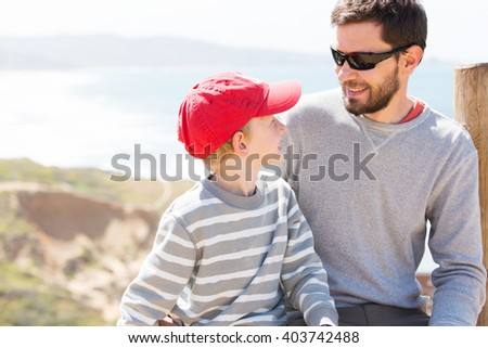positive smiling father with a beard and his cheerful son sitting together and enjoying nice weather at the beach, emotion concept - stock photo