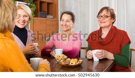 Positive smiling female pensioners drinking coffee and talking at home
