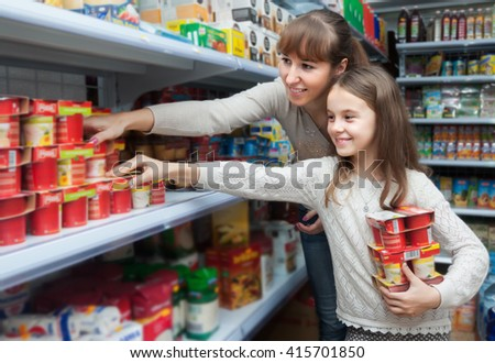 Positive smiling female with daughter buying sweet yoghurts in dairy section - stock photo