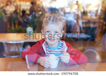 positive smiling little boy eating ice-cream at cafe, view through the window - stock photo