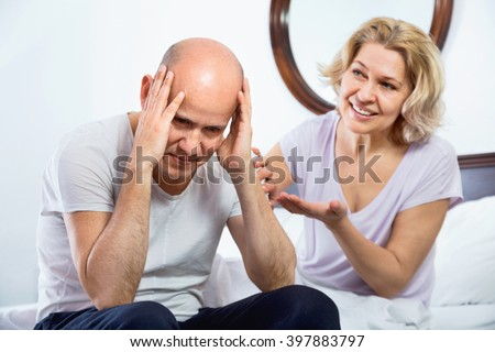 Positive smiling mature girl supporting frustraited boyfriend in difficuilt moment