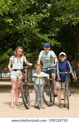 Positive smiling parents with children traveling through city by bicycles