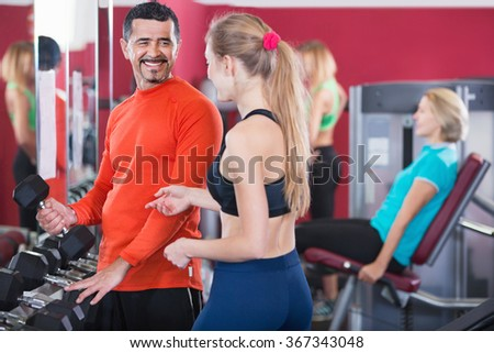 Positive smiling people  weightlifting training in modern health club