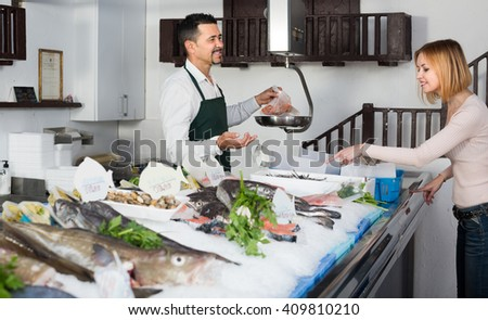 Positive smiling seller in apron selling chilled fish to young female in fish store - stock photo