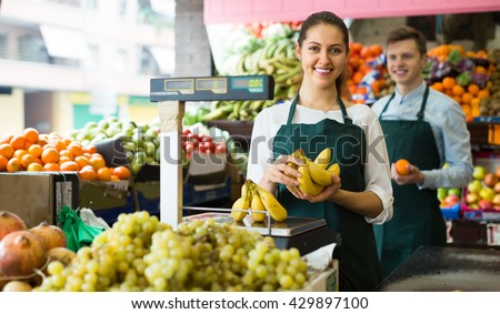 Positive smiling sellers weighing stems of sweet bananas at fruit market
