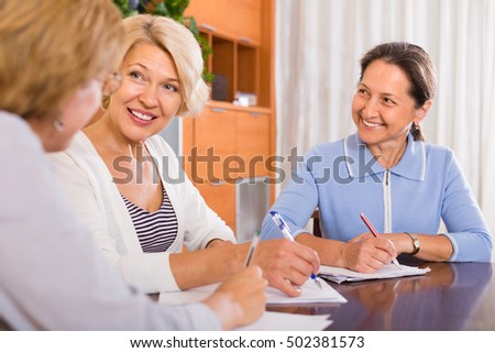 Positive smiling senior ladies signing documents at notary. Focus on brunette