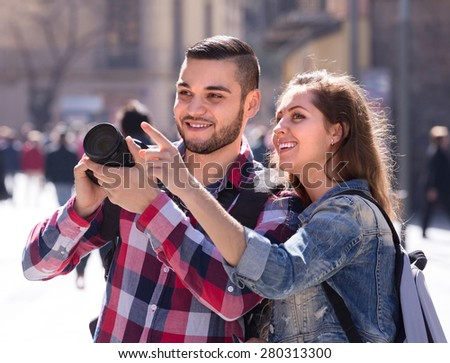 Positive smiling travelers going sightseeing with camera through square of European city