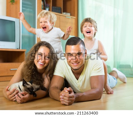 Positive smiling young family of four laying on the floor in living room with kitten. Focus on man  - stock photo