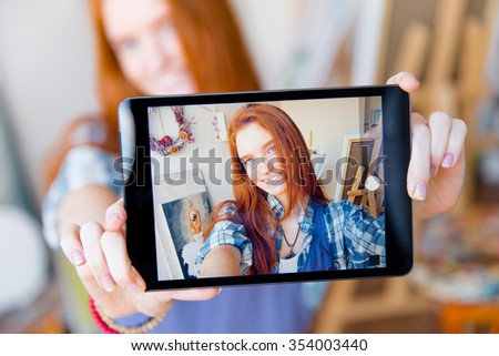 Positive smiling young redhead woman making selfie using tablet in artist workshop - stock photo