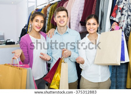 positive spanish adults in good mood holding bags at clothing store