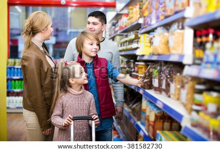 positive spanish parents with two kids choosing crispy flakes in shop
