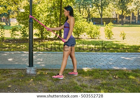 Positive sporty female exercising with trx strips in an autumn park.