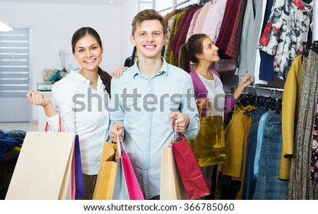 Positive spouses carrying bags with purchases and smiling in boutique