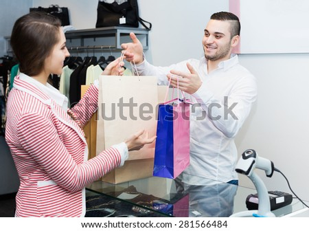 Positive store clerk serving purchaser at cash register desk - stock photo