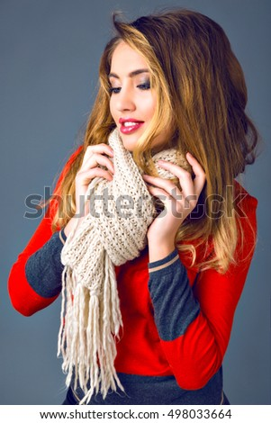 Positive studio fashion lifestyle autumn winter portrait, cheerful blonde woman holding with her scarf, smart casual outfit, sweater, brought sexy makeup, fluffy hairstyle.