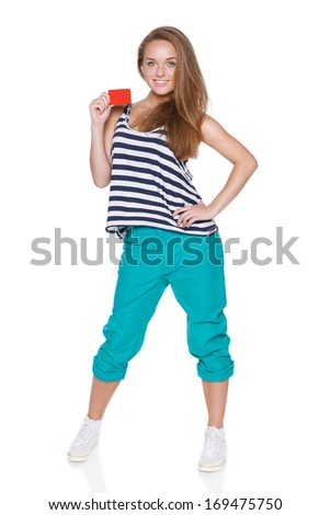 Positive teen girl hipster in casual summer clothes standing in full length and showing blank credit card, over white background - stock photo