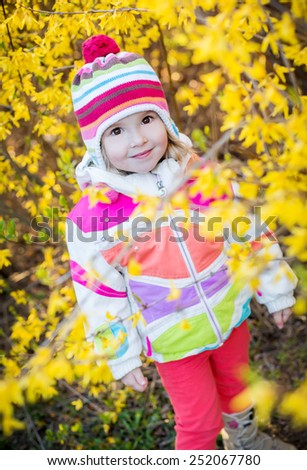 Positive toddler girl  on the background of yellow flowers spring time - stock photo