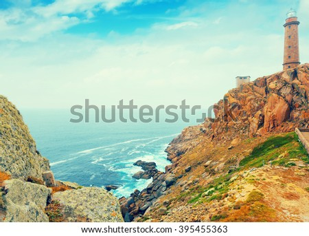 Positive toned photo with  lighthouse on the rocky coast